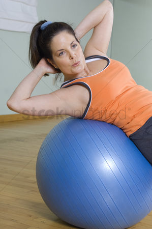Posed : Woman doing sit-ups with exercise ball