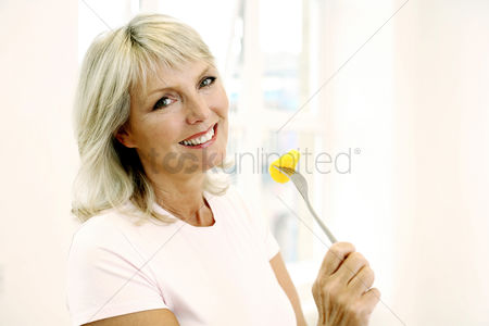 Smiling : Woman enjoying fruit