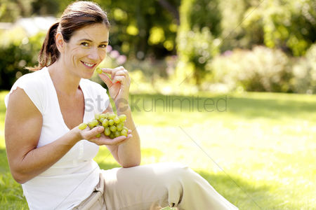 Aging process : Woman enjoying green grapes in the park