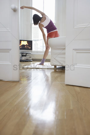 Flat : Woman exercising and watching television in living room back view