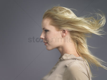 Blowing : Woman facing the wind hair billowing behind profile close-up