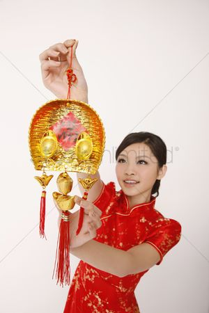 Traditional clothing : Woman hanging chinese new year decorative item