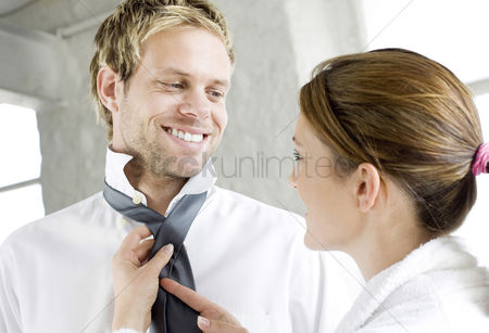 Cheerful : Woman helping her husband with his tie