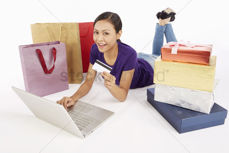 Femininity : Woman holding a credit card while using laptop