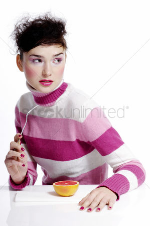 Composed : Woman holding a fork with an orange on the table