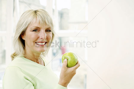 Smiling : Woman holding a green apple