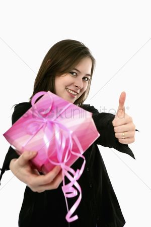 Birthday present : Woman holding a present and showing thumbs up