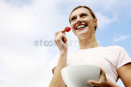 Smile : Woman holding a strawberry and a bowl