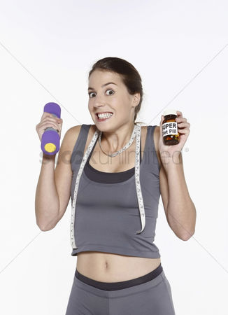 Dumbbell : Woman holding dumbbell and a bottle of diet pills