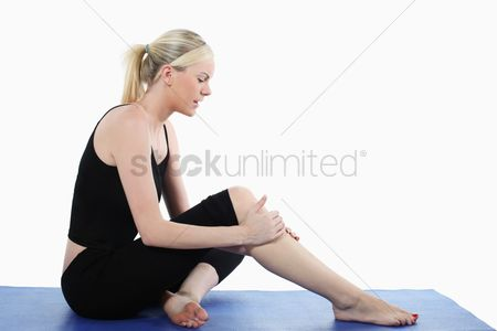 Body : Woman holding her knee while sitting on yoga mat