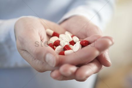 Medication : Woman holding medicine pills in clasped hands close up on hands
