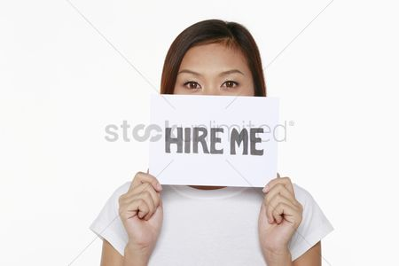 Unemployment : Woman holding placard with text  hire me