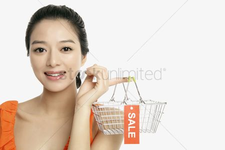Shopping background : Woman holding shopping basket with sale label