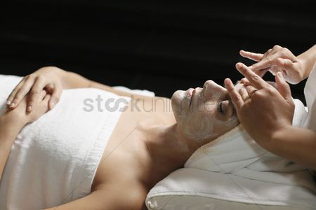 Refreshment : Woman in health spa  having cream applied to face