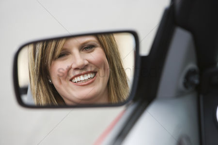 Smile : Woman in side-view mirror of car