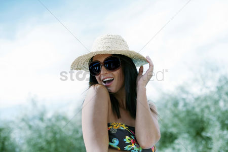 Cheerful : Woman in straw hat and sunglasses posing for the camera