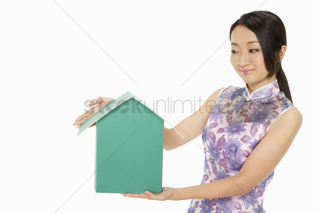 Lunar new year : Woman in traditional clothing holding up a cardboard house