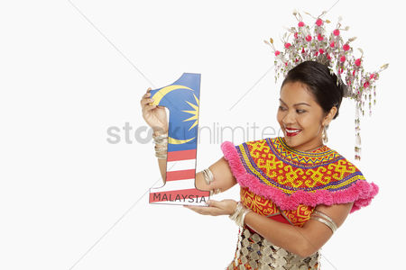 Bidayuh ethnicity : Woman in traditional clothing holding up a number one shape