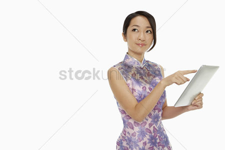 Lunar new year : Woman in traditional clothing using a digital tablet