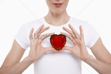 Young woman : Woman in white t-shirt holding red glass heart in both hands