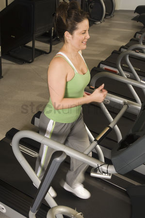 Workout : Woman jogging on treadmill at health club