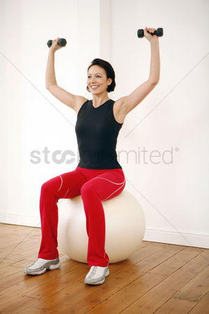 Strong : Woman lifting dumbbells while sitting on a fitness ball