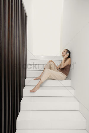 Stairs : Woman listening to music on the headphones