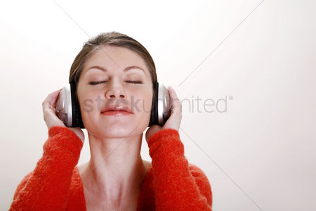 Head shot : Woman listening to music on the headphones