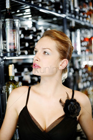 Sets : Woman looking at the selection of wine in the wine cellar