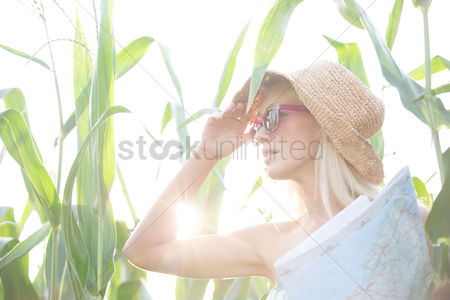 Assistance : Woman looking away while holding map amidst plants on sunny day