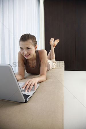 Lying forward : Woman lying forward on sofa with legs up