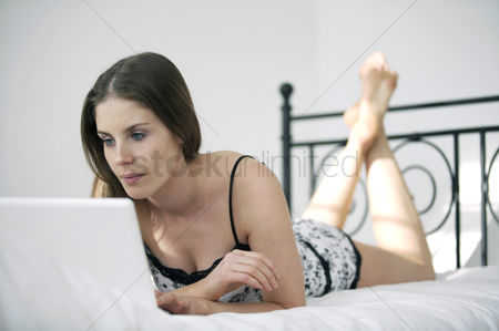 Lying forward : Woman lying forward on the bed using laptop
