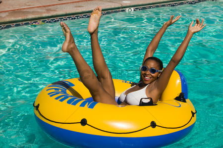Arm raised : Woman lying on inflatable raft in swimming pool with arms and legs raised portrait