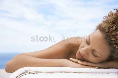 Curly hair : Woman lying on massage table head and shoulders eyes closed