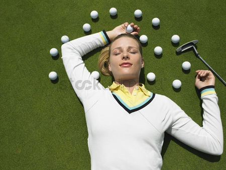 Sports : Woman lying on putting green with golf balls