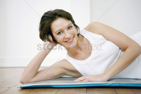 Smiling : Woman lying on yoga mat