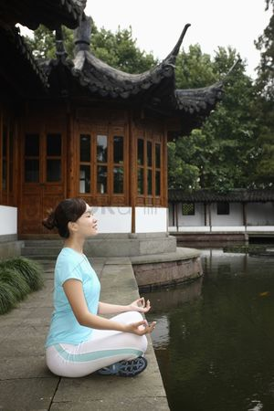 Practising yoga : Woman meditating by the lakeside  eyes closed