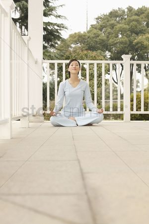 Practising yoga : Woman meditating on the porch