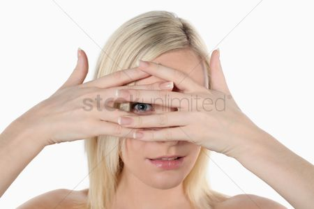 British ethnicity : Woman peeking in between her fingers