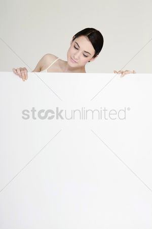 Cardboard cutout : Woman peeking out from behind blank placard
