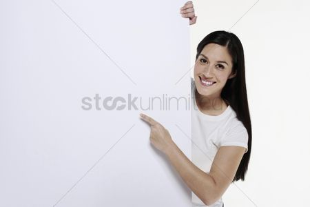 Cheerful : Woman pointing at white placard
