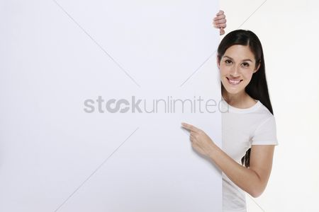 Smiling : Woman pointing at white placard