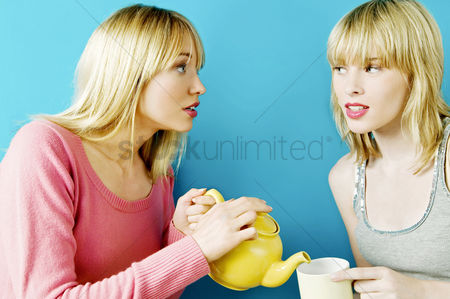 Friend : Woman pouring tea for her friend