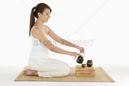 Tea pot : Woman pouring tea into a cup