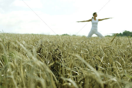 Three quarter length : Woman practicing yoga on the field