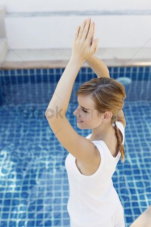 Practising yoga : Woman practising yoga by the pool side