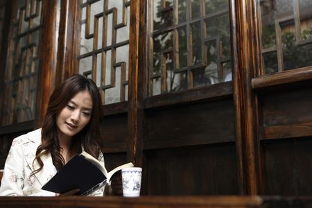 China : Woman reading book in restaurant