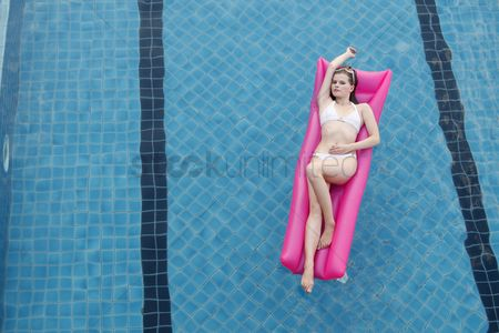 Arm raised : Woman relaxing on inflatable raft in pool