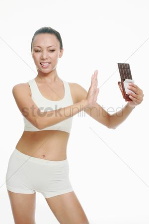 Forbidden : Woman restricting herself from eating a bar of chocolate