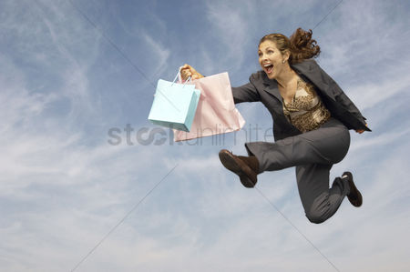 Ponytail : Woman running with shopping bags mid-air outdoors